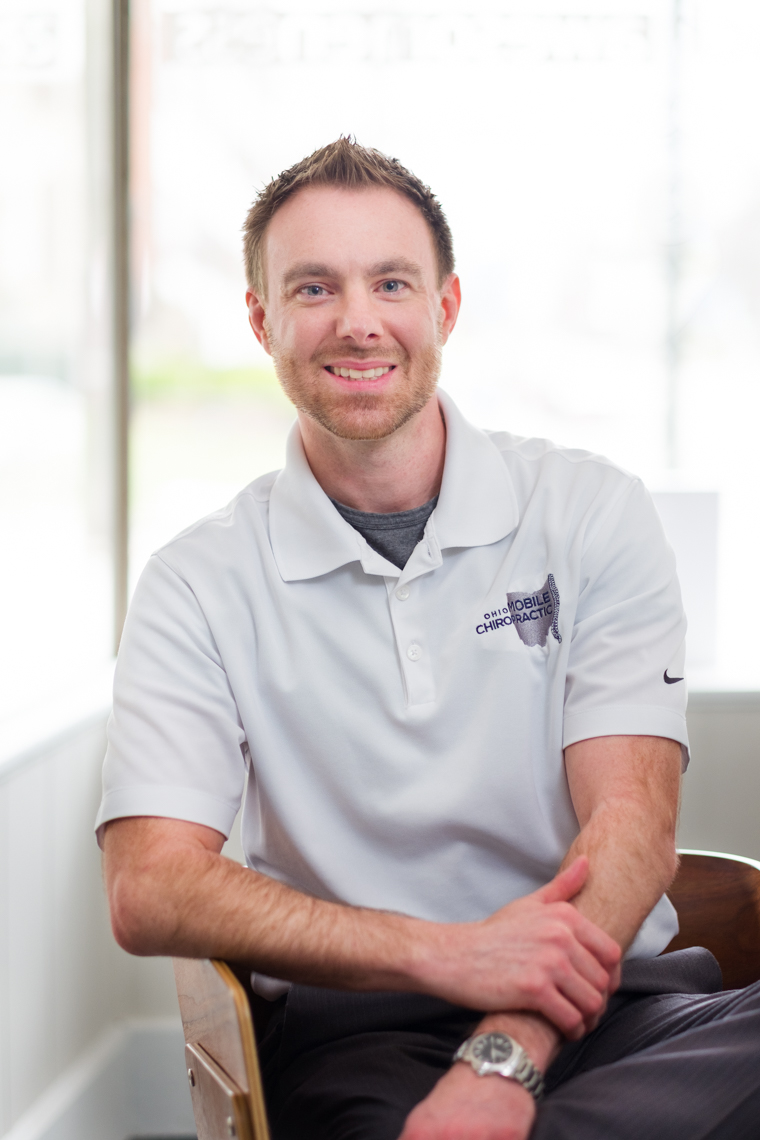 Business headshot of a chiropractor by a window.