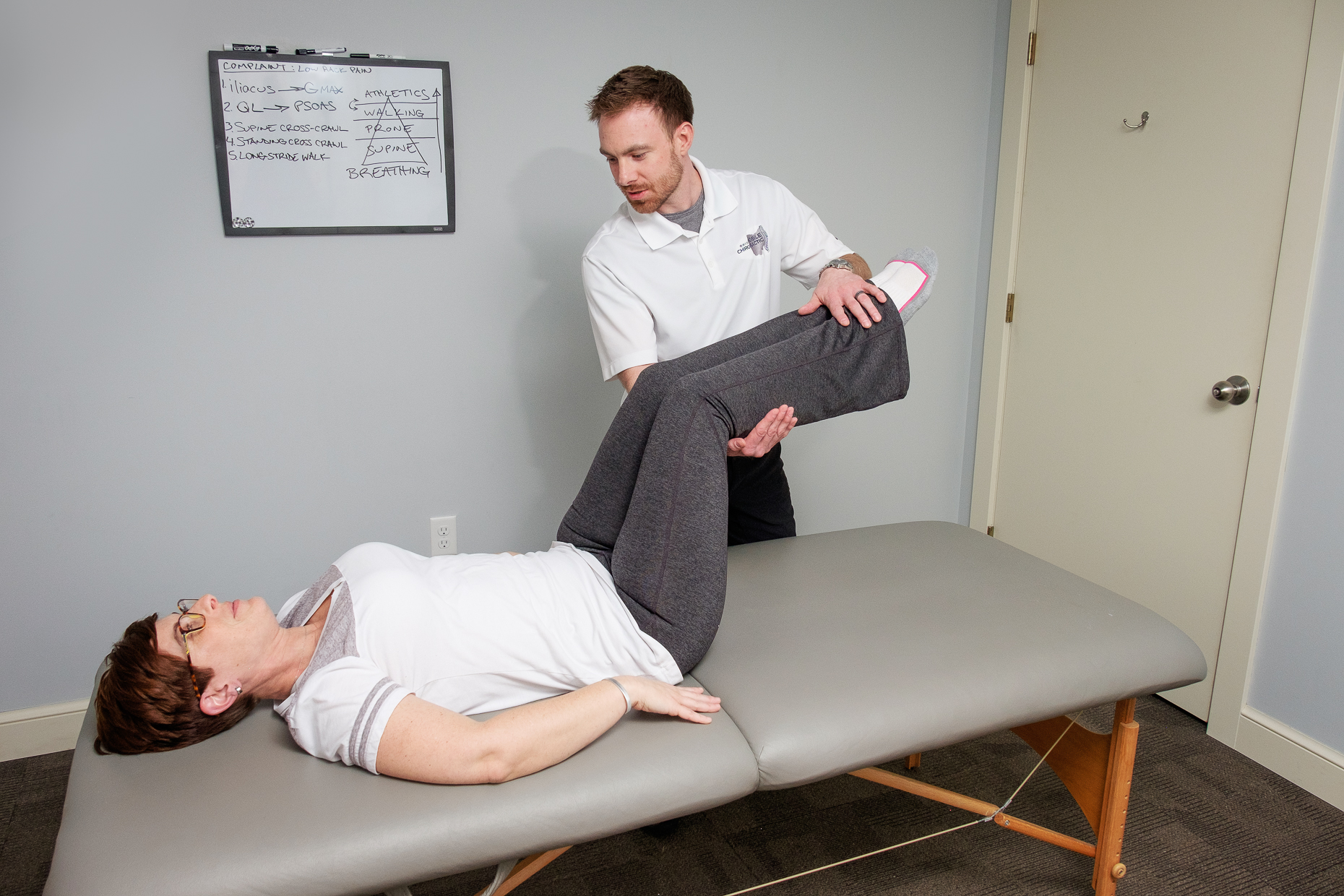 A chiropractor working with a client in their office.