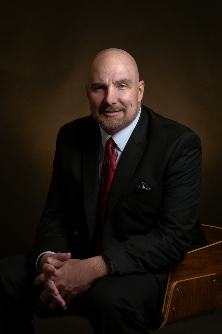 Business headshot of male professional on dark background.
