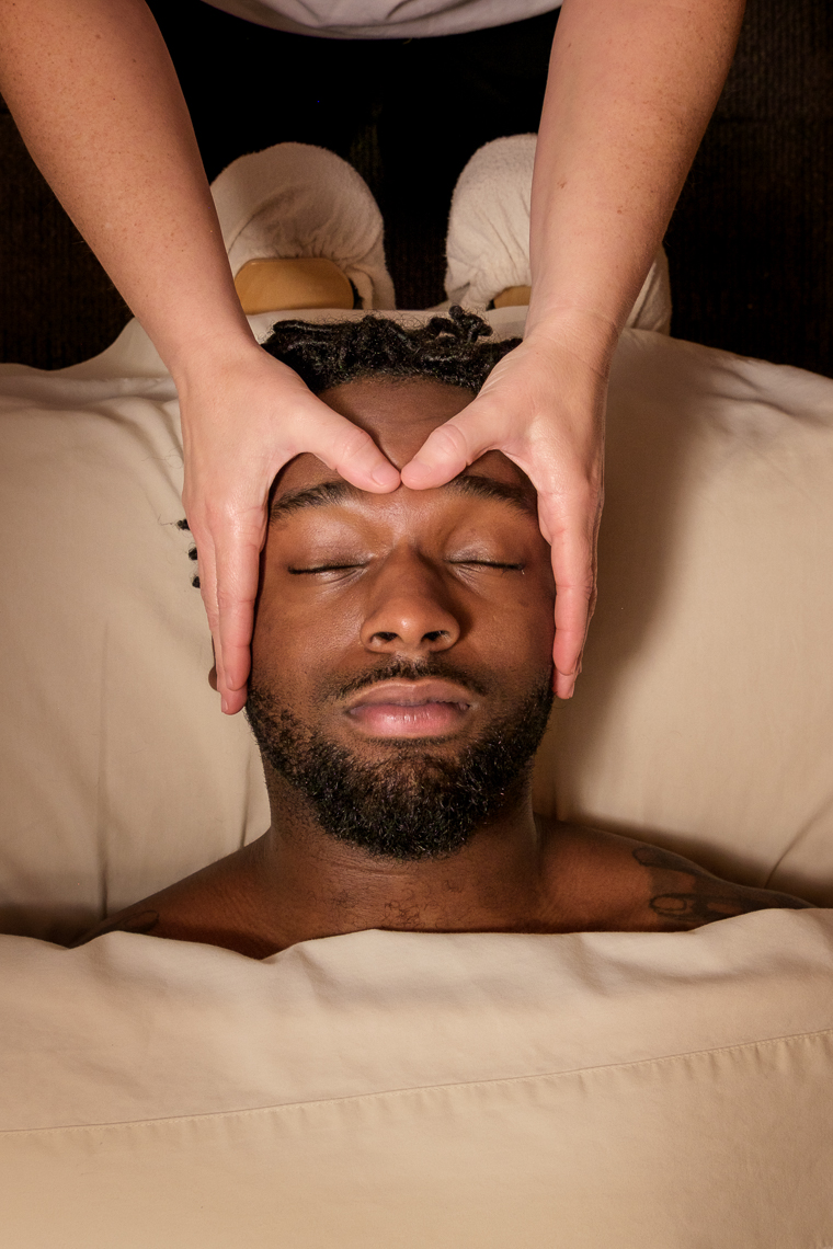 A young man on a massage table getting massaged.