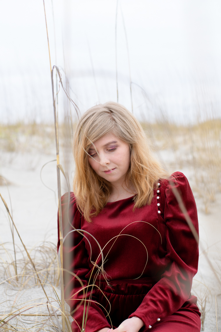a young woman on a beach looking away from the camera.